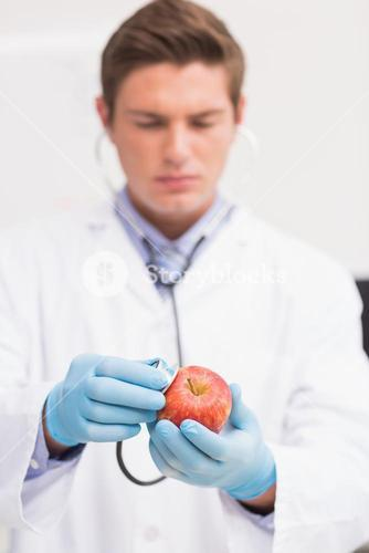 Scientist listening apple with stethoscope