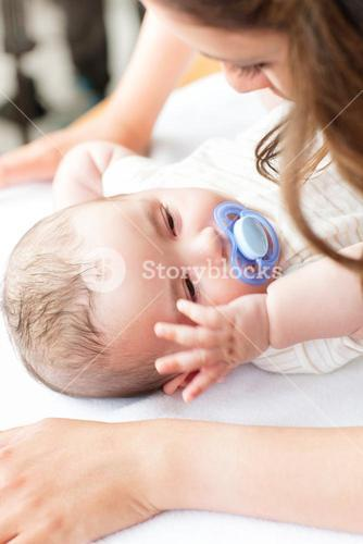 Close up of a baby lying on a changing table while his mother is changing his nappy