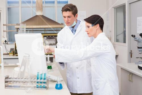 Scientists looking attentively at computer
