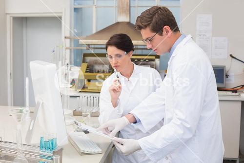 Scientists working attentively with computer