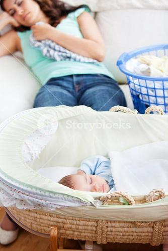 Cute baby sleeping in his cradle with his mother lying on the couch in the background
