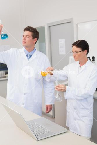 Scientists working attentively together with beakers
