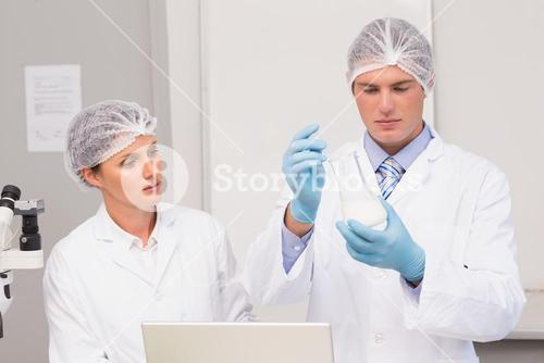 Scientists working attentively with beaker