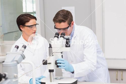 Scientists looking attentively in microscope
