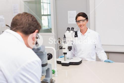 Scientists looking attentively in microscopes