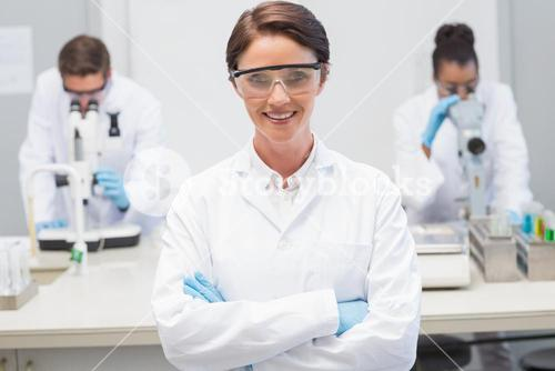 Happy scientist smiling at camera with protective glasses