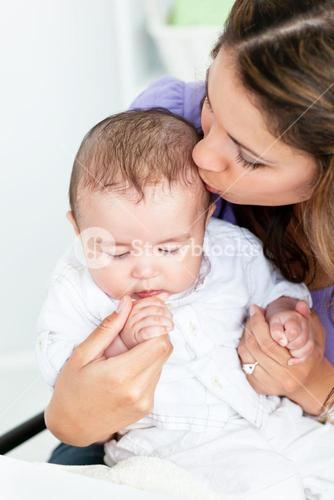 Portrait of an adorable mother kissing her baby iin the kitchen