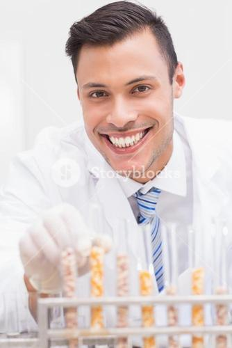 Happy scientist looking at camera with tubes of corn and kernel