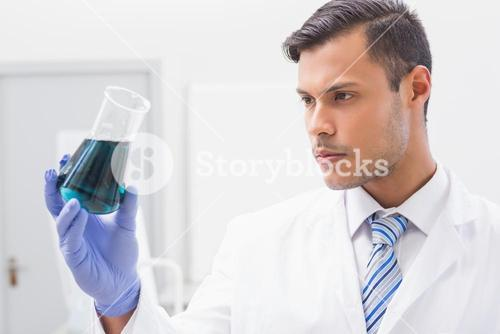Concentrated scientist looking at beaker