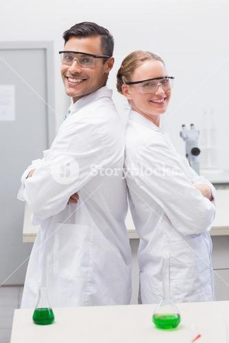 Smiling scientists standing back to back