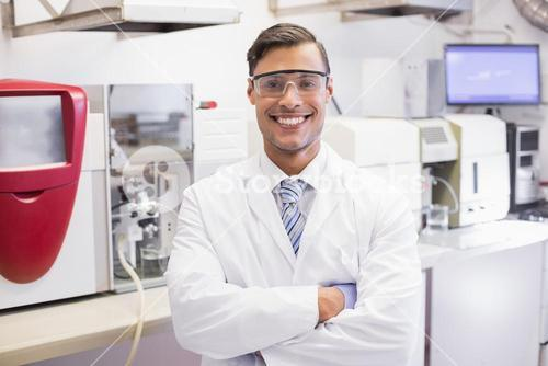 Smiling scientist looking at camera arms crossed