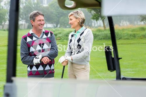 Happy golfing couple laughing