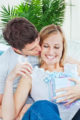 Attentive man kissing her girlfriend after giving her a present both lying on the couch
