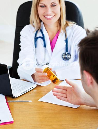 Portrait of an attractive doctor giving pills to her patient during an appointment