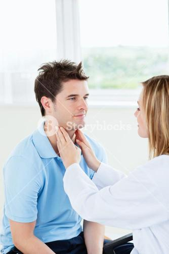 Female doctor examinating the throat of a happy patient sitting in her office