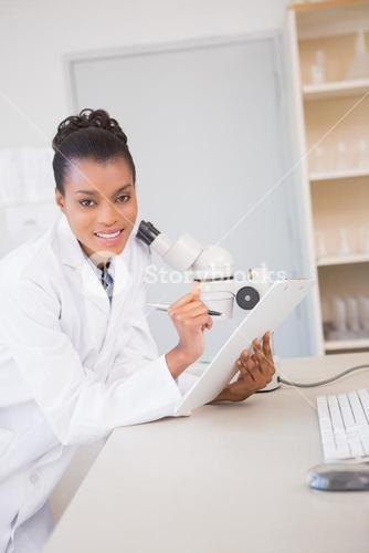 Smiling scientist looking at camera and taking notes