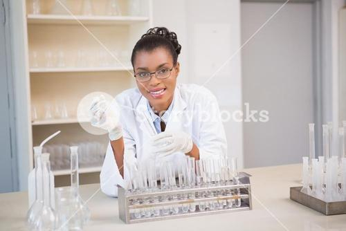 Smiling scientist working with pipette
