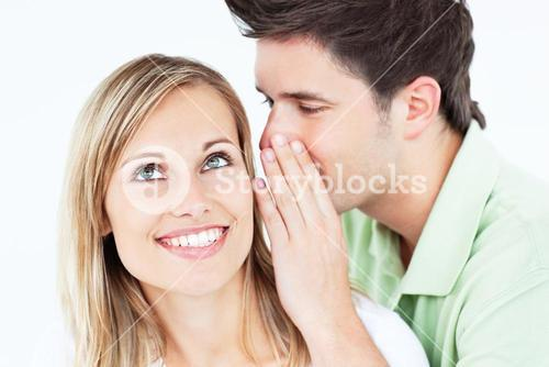Young man whispering something to his attentive female friend