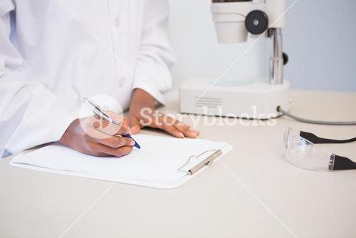 Concentrated scientist taking notes