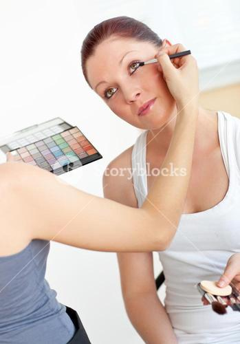 Close up of a woman makingup her female friend at home