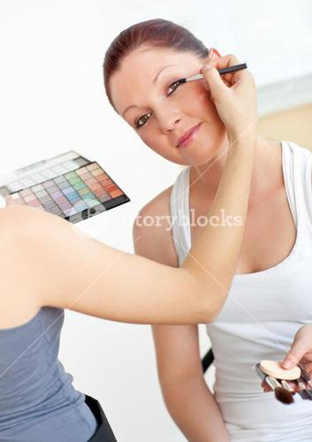 Happy young woman with makeup accessories being made-up by a friend