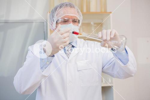 Scientist injecting red liquid in flask