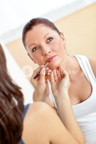 Young woman makingup her friend using lipstick and eye shadow