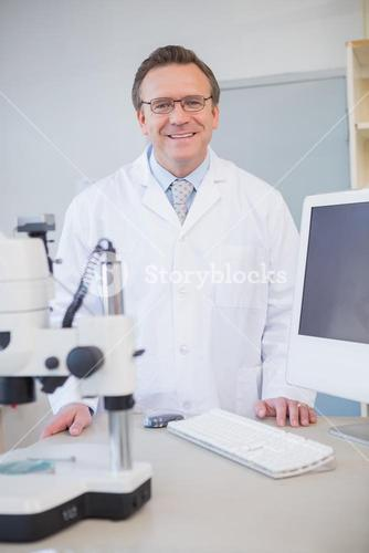 Happy scientist looking at camera with hands on table