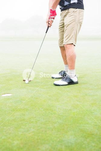 Golfer on the putting green at the hole