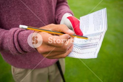 Golfer writing his points in paper