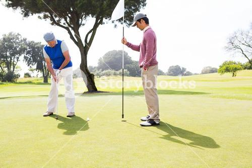 Golfer swinging his club with friend