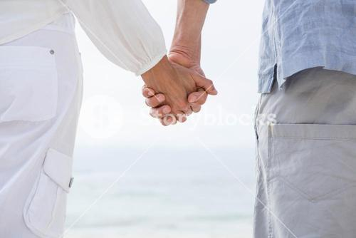Happy couple holding hands and looking at the sea