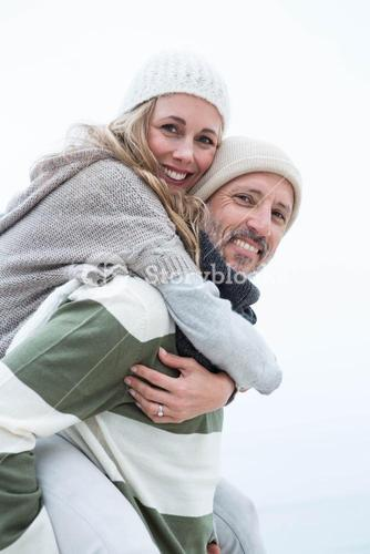 Smiling man giving his partner a piggy back