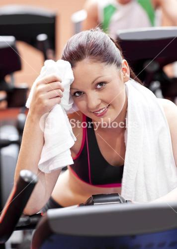 Attractive woman wiping her face after exercises on a bicycle in a sport centre