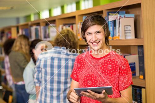 Student using digital tablet in library