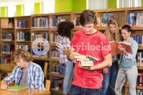 Male college student holding books in library