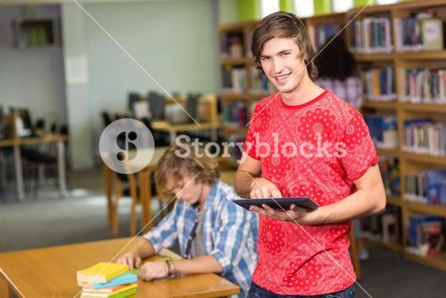 Male college student using digital tablet in library