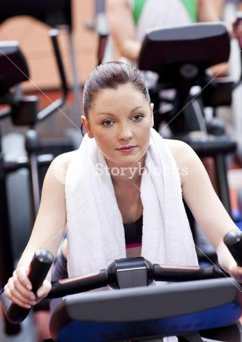 Serious athletic woman pedaling during a training in a sport centre