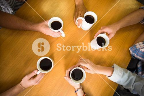 Hands holding coffee mugs on table