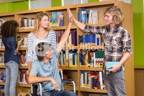 Students high fiving in library