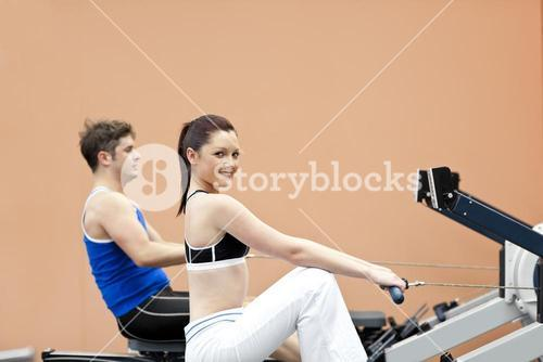 Positive woman with her boyfriend using a rower in a sport centre