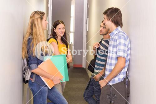 Students with files standing at college corridor