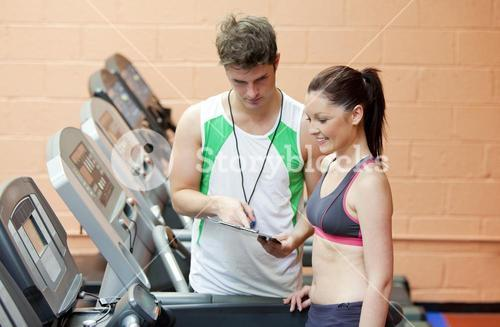 Serious coach giving instruction to a female athlete standing on a treadmill