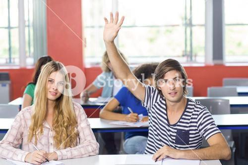 Male student raising hand in classroom