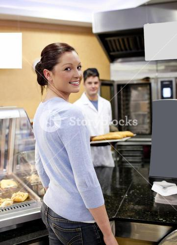 Attractive woman buying baguette in a cafeteria with baker in the background