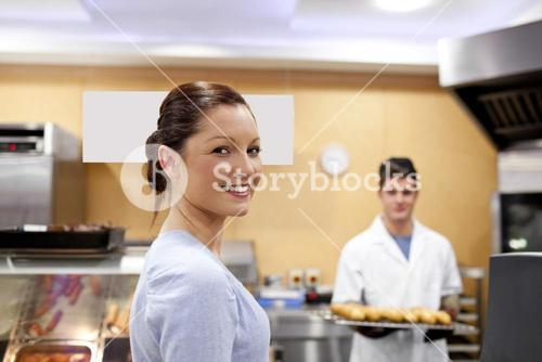 Beautiful woman in a cafeteria buying baguette from a baker standing in his kitchen