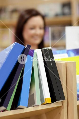 Close up of a book shelf in a library with female customer in the background