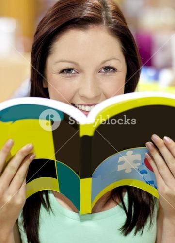 Portrait of a beautiful woman holding a book in a library smiling at the camera