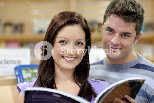 Portrait of a cute couple reading a book in a shop