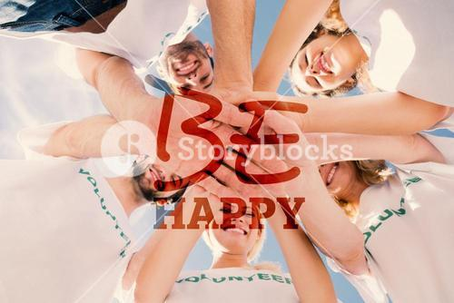 Composite image of happy volunteers with hands together against blue sky
